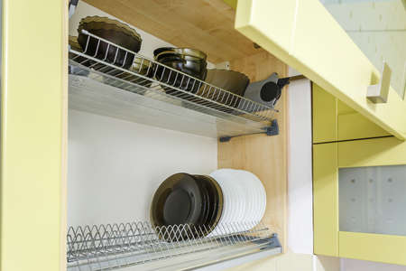 set of plates, cups on the shelf in the kitchen cabinet