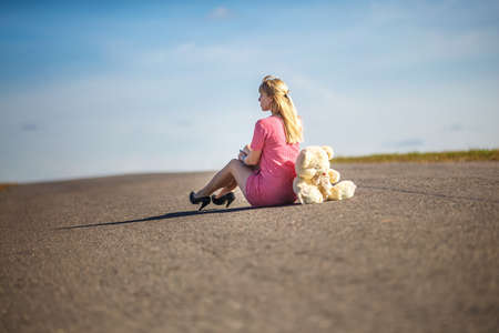 girl in plaid suit sits on asphalt road with teddy bear. concept of loneliness waiting for happiness