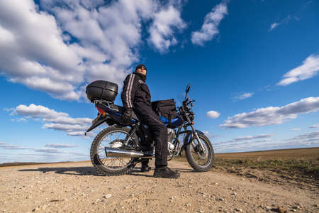man in a black uniform on bike against the backdrop of panorama of field and blue sky. motorcycle travel concept