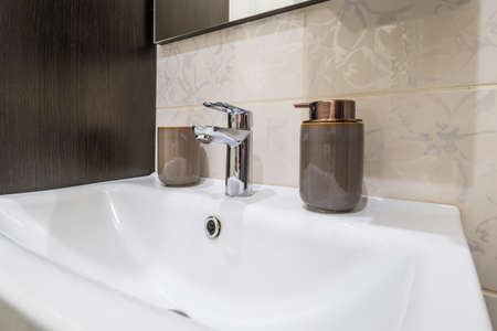 metal water tap sink with faucet with soap and shampoo dispensers in expensive bathroom Archivio Fotografico