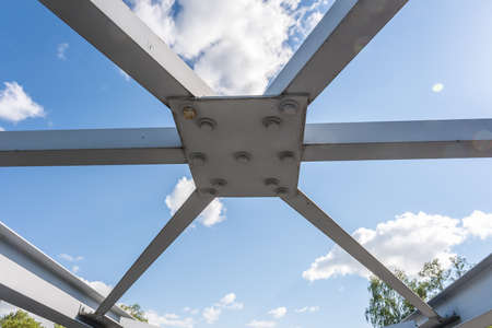 iron steel frame construction of bridge on blue sky background. bridge metal structures, frames, bolts and nuts