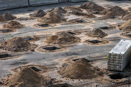 rows of pits at a construction site. preparation of the site for the installation of piles. a pile of sand