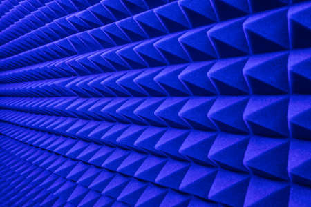 rows of acoustic music soundproof foam pyramid panel with blue lighting.