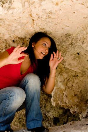 cave exploring: Young woman exploring rocky cave