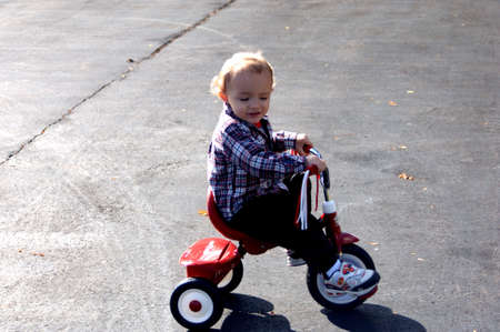 Toddler riding tricycle on asphalt