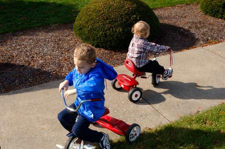 Boys riding trikes Stock Photo