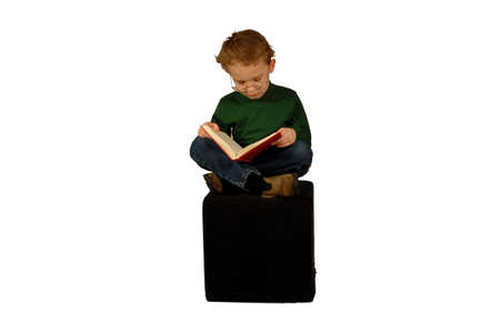 Young boy sitting reading book