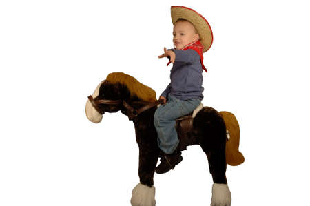 Young boy dressed as cowboy next to toy horse photo