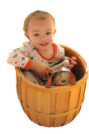 Young boy sitting in wicker basket Stock Photo