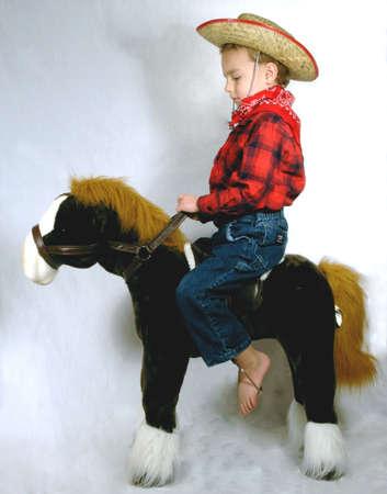 Boy sitting on toy horse Stock Photo