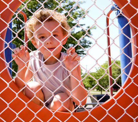 Young boy looking through fence playing prisoner