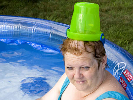 Woman sitting in swimming pool with bucket on head