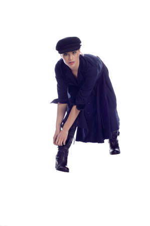 bending over: Beautiful model in black with hat bending over fixing black leather boot Stock Photo