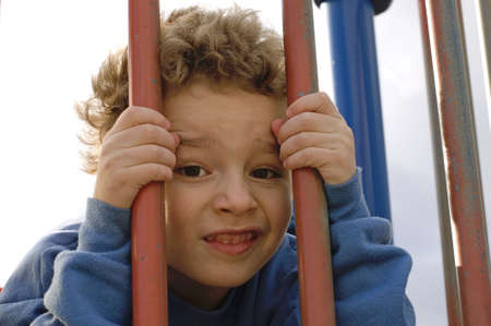 Young boy behind bars on playground equipment Stock Photo