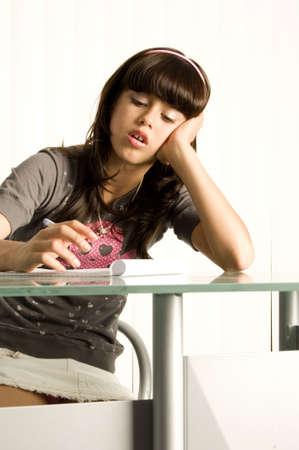 Teenager doing homework at desk looking confused