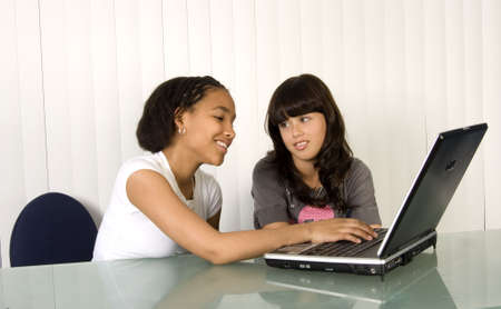 Teens on laptop computer at desk doing instant messaging