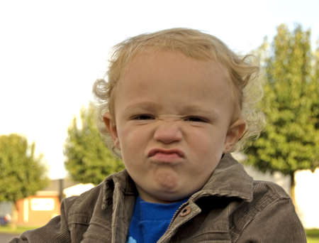 pouty: Young boy outside giving pouty look on his face Stock Photo