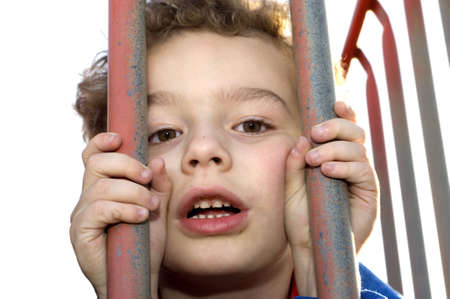 Young boy playing prisoner behind bars at playground