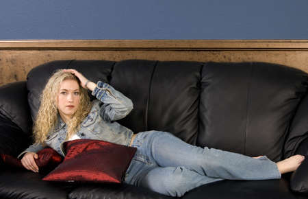 woman on couch: Beautiful blond curly haired model laying on black couch Stock Photo