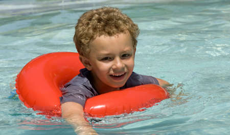 curls: Young boy in float ring in swimming pool Stock Photo