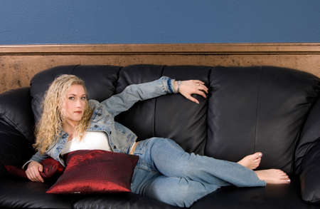 woman on couch: Beautiful blond model laying on black leather couch