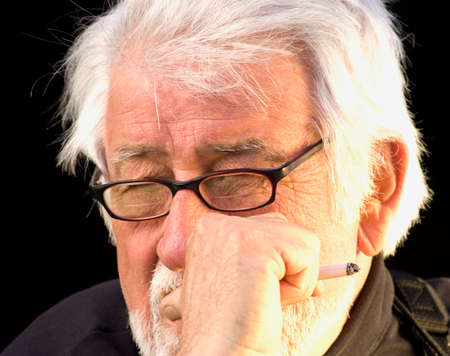 bifocals: Whited haired man contemplating life while smoking a cigarette