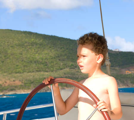 curls: Young boy driving or steering a boat in the ocean