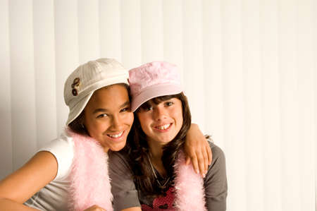 Two teenage girl friends hugging each other and smiling
