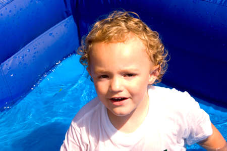 curls: Young boy sitting in pool of water in hot summer sun Stock Photo