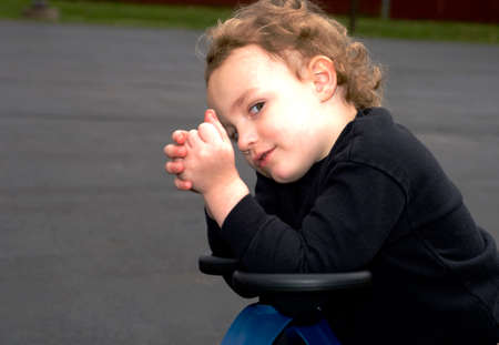 Young boy giving sideways sly glance while sitting outside Stock Photo