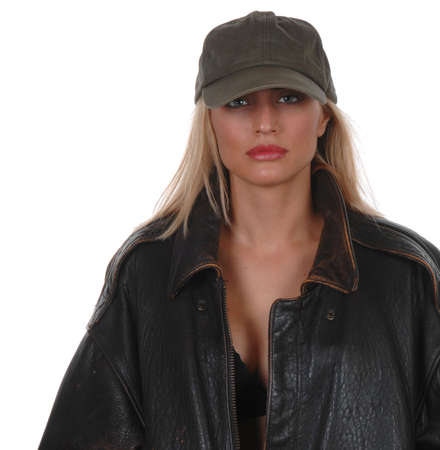 Beautiful model looking tough in brown leather jacket with baseball cap Stock Photo