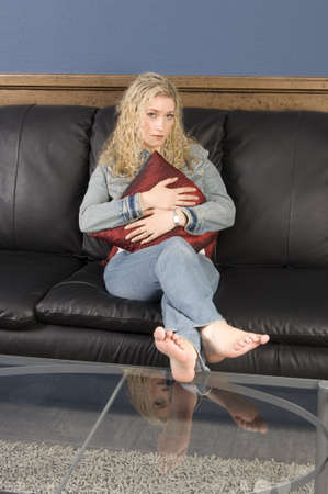 woman on couch: Beautiful blond, sitting on black leather couch holding red pillow Stock Photo