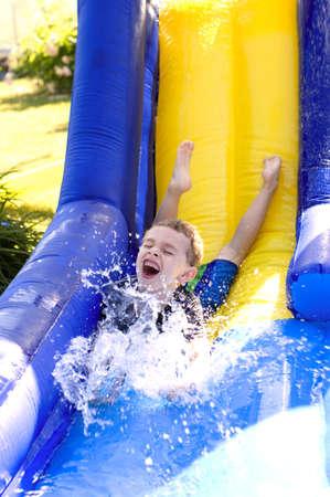 Young boy splashing water at bottom of water slide