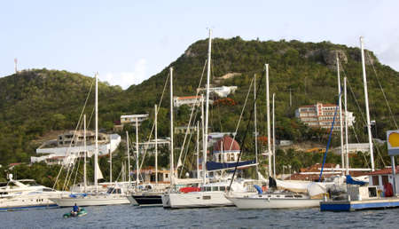 simpson: Boats docked at marina with mountains and houses in background Stock Photo