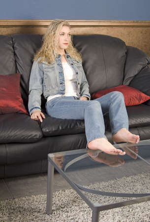 couch: Beautiful blond model sitting on black leather couch