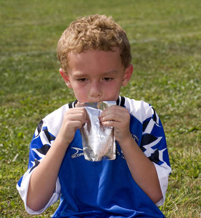 Young boy drinking from a pouch at soccer game halftime