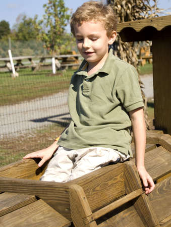 curls: Young boy sitting on wooden playground equipment smiling