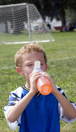 Young boy having orange drink during halftime of soccer game Stock Photo