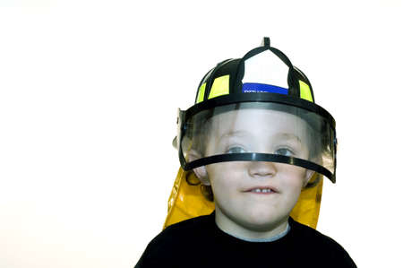 Young boy wearing toy fire helmet with shield photo