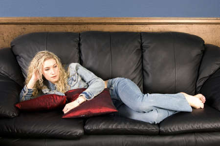 red sofa: Beautiful blond model relaxing on black leather couchsofa