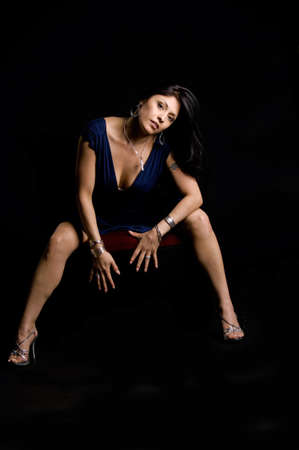 leaning forward: Beautiful model sitting leaning forward in blue dress Stock Photo