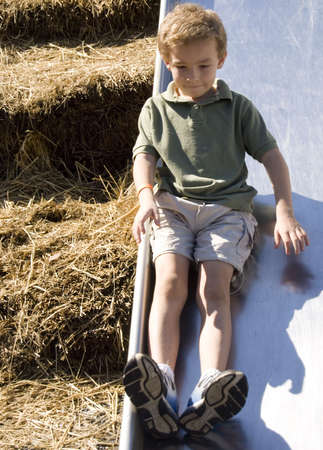 curls: Young boy on playground slide with straw bales in background