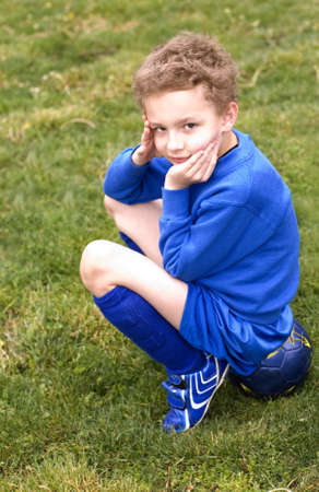 uniform curls: Soccer player waiting on sidelines Stock Photo