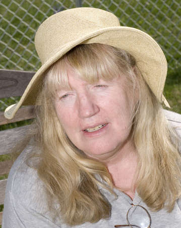 squinting: Woman wearing straw squinting eyes sitting on bench