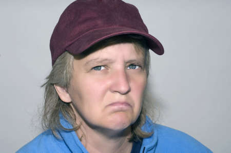 miserable: Old woman wearing baseball hat looking grumpy and miserable Stock Photo