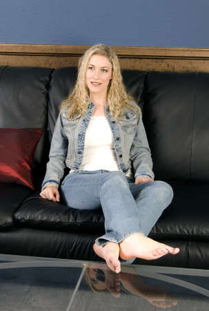 denim jacket: Beautiful blond model sitting on black leather couch relaxing Stock Photo