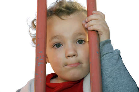waiting convict: Young boy looking from behind orange bars