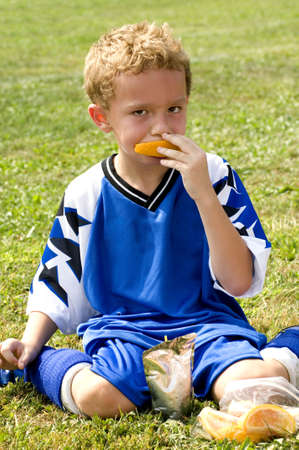 Young soccer player having halftime snack of orange and drink pouch Stock Photo