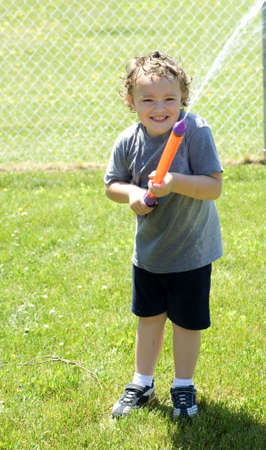 Young boy spraying water from gun in the summer photo