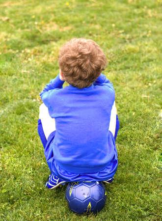 uniform curls: Back of soccer player sitting on ball on sideline